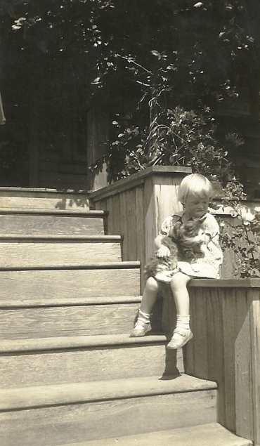 My mother, as a child, on the same steps holding a cat.
