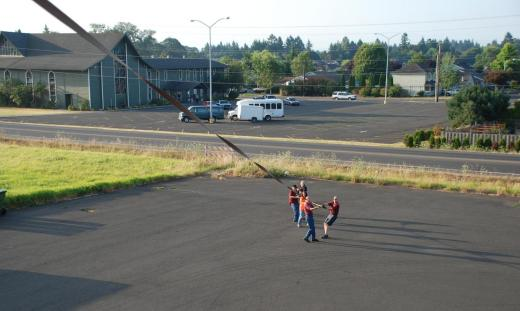The ground crew hold the anchor line as Chris lowers the balloon to the asphalt.