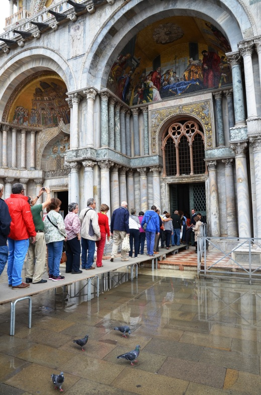 Tourists wait in line to see the Basilica during high tide