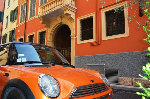A colorful building in Verona, with a marching Mini Cooper parked across the narrow street