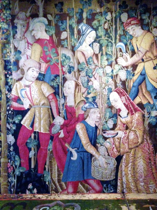 A tapestry showing wine making